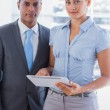 Business team with tablet pc smiling at camera — Stock Photo #26994401