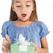 Surprised little girl holding a wrapped gift — Stock Photo #26995083
