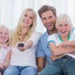 Happy family sitting on couch — Stock Photo #26995421