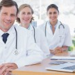 Happy group of doctors posing at their desk — Stock Photo