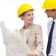 Architect team looking at each other with construction plan — Stock Photo