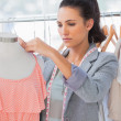 Stock Photo: Attractive designer adjusting,dress on a mannequin