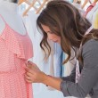 Fashion designer measuring dress on a mannequin — Stock Photo #26996339