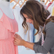 Stock Photo: Fashion designer measuring dress on a mannequin