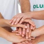 Volunteers putting hands together — Stock Photo