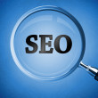 Magnifying glass revealing the word SEO — Stockfoto