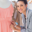 Stock Photo: Attractive fashion designer adjusting dress