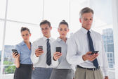 Team of business standing together in line with their mobile — Stock Photo