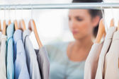 Fashion woman choosing clothes on clothes rail — Stok fotoğraf