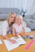 Smiling mother drawing with her little girl — Stock Photo