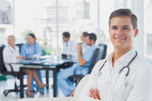 Smiling doctor with arms folded standing — Stock Photo