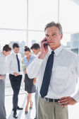 Serious boss on the phone standing in a modern office — Stock Photo