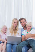 Portrait of a cheerful family using a laptop — Stock Photo