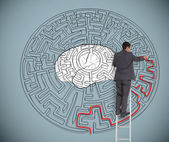 Businessman trying to solve a large maze with a brain illustration — Stock Photo