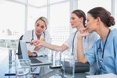 Arts iets op een laptop aan haar collega's weergegeven — Stockfoto