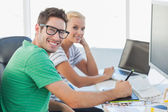 Attractive photo editors working together on graphics tablet — Stock Photo
