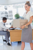 Businesswoman holding a box and his colleagues in the bottom — Stock Photo