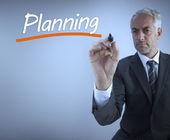 Businessman writing the word planning — Stock Photo