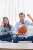 Woman looking at her husband cheering the basketball game — Stock Photo