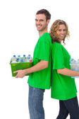 Cheerful activists holding box of recyclables and standing back — Stock Photo