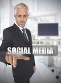 Businessman touching the term social media — Stock Photo
