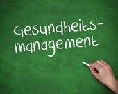 Χέρι που γράφει gesundheits διαχείρισης — Φωτογραφία Αρχείου
