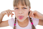 Little girl clogging her ears and wincing — Stock Photo