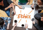 Team brainstorming over a poster with ethics written on it — Stock Photo