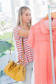 žena stojící a při pohledu na oblečení — Stock fotografie