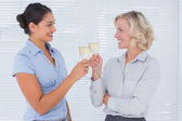 Two cheerful colleagues clinking their flutes of champagne — Stock Photo