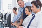 Smiling manager helping call centre employee — Stock Photo