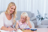 Smiling mother and daughter drawing — Stock Photo
