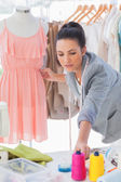 Beautiful fashion designer adjusting dress — Stock Photo