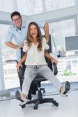 Cheerful designers having fun with a swivel chair — Stock Photo