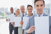 Business team in a line holding blank pages — Stock Photo
