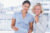 Cheerful businesswomen holding digital tablet — Stock Photo