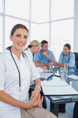 Attractive doctor sitting in front of her team — Stock Photo