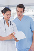 Doctor and surgeon reading over notes on clipboard — Stock Photo