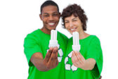 Cheerful activists holding energy saving light bulbs — Stock Photo