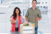 Smiling volunteers taking out food from donations box — Stock Photo