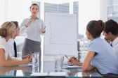 Businesswoman giving explication in front of a growing chart — Stock Photo