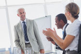 Colleagues applauding smiling manager during a meeting — Stok fotoğraf