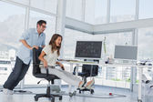 Designers having fun with a swivel chair — Stock Photo