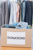 Donations box full of clothes in front of clothes rail — Stok fotoğraf