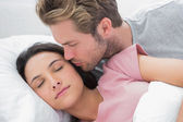 Man kissing his sleeping wife on the cheek — Stock Photo