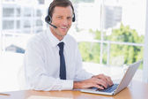 Cheerful businessman wearing a headset — Stock Photo