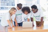 Voluntários trabalhando juntos em um laptop — Fotografia Stock