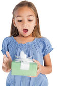 Surprised little girl holding a wrapped gift — Stock Photo