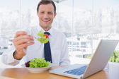 Smiling businessman eating a salad — Stock Photo