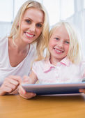Mother using tablet pc with her daughter — Stock Photo